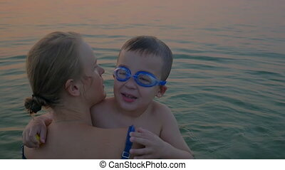 Hugs and kisses of mother with son in the sea - Slow motion...