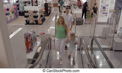 Young family with child riding escalator in shopping center...
