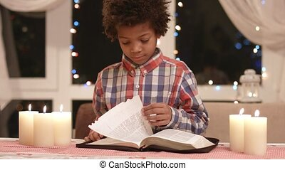 Mulatto boy turning book pages. Kid with book on Christmas....