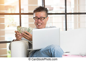 happy asian senior male with cash and laptop
