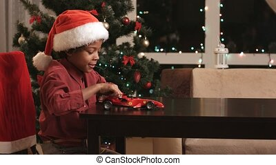 Boy playing with toy car. Christmas kid with toy car. Little...