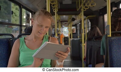 Happy pretty blonde with tablet PC riding in the bus - Slow...