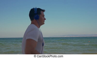 Man jogging with music at the seaside