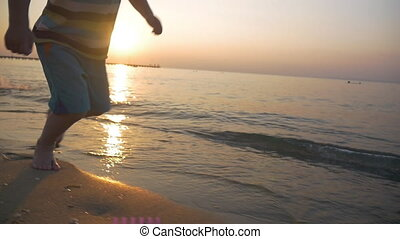 Child running barefoot along the sea at sunset - Slow motion...