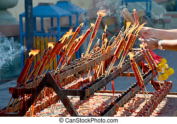 People burning incense and red candle for pray god