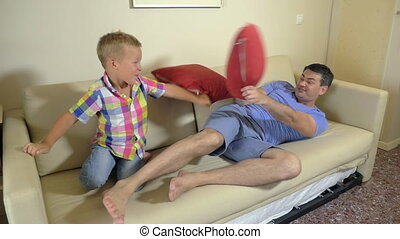 Dad and son fighting with cushions - Slow motion of young...