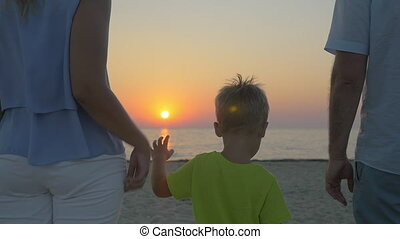 Family with child looking at sunset over sea