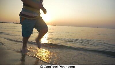 Barefoot kid running in sea water at sunset