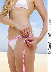 Bikini body: Woman measuring her hips on the beach - Bikini...