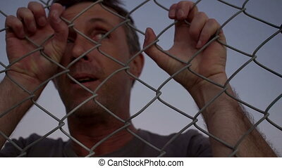 Male Struggling Behind a Wire Fence - Closeup dusk shot of a...