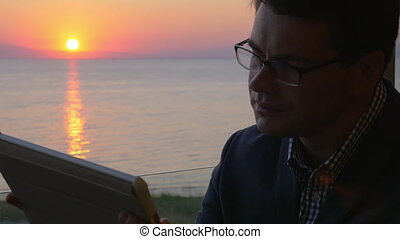 Man working with pad on the balcony at sunset - Slow motion...