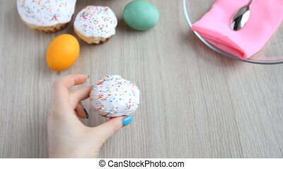 Hands put on the table Easter cake with white icing - Female...