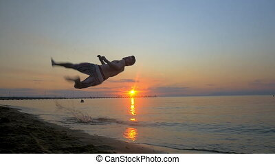 Athlete doing acrobatic tricks on the beach at sunset - Slow...