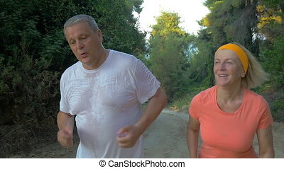 Senior couple jogging in the forest - Slow motion steadicam...