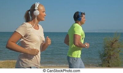 Couple in headphones jogging along the sea front - Slow...