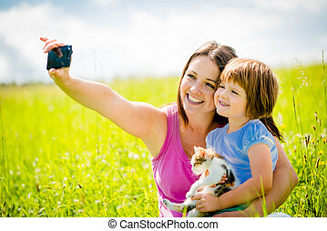 Selfie - mother, child and kitten - Mother taking photo with...