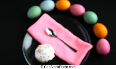 On black table lay different colored eggs, Easter cake, plate spoon, and napkin.