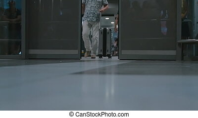 Men with suitcases walking through the doors at airport -...