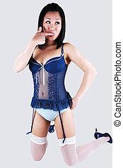 Pretty Asian girl kneeling in lingerie.