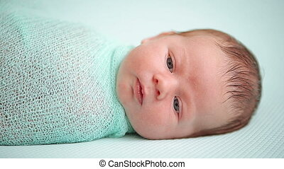 Blue-eyed newborn baby lying and looking around in wonder HD