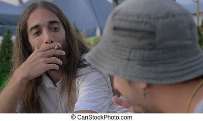 Men friends talking and smoking in outdoor cafe - Slow...