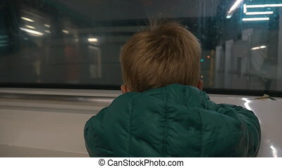 Little child looking out subway train window - Slow motion...