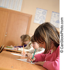 School lesson - Cute schoolchildren are writing using...