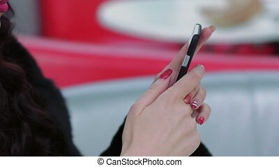Smartphone in elegant woman's hands with pink nails and lips. Slowly