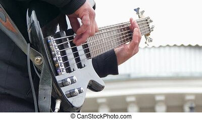 Hands Of Man Playing Electric Bass Guitar - CLOSE UP shot of...