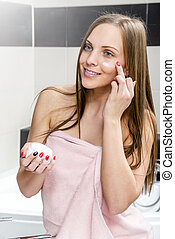 Putting anti-aging cream - Attractive girl putting...