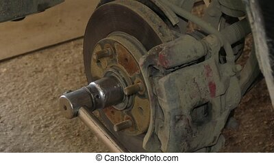 Mechanic Dismantling Brake Disk Of Car - CLOSE UP of...