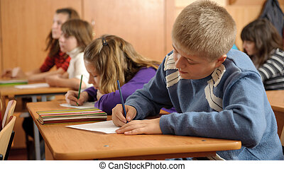 Diligent schoolboy is writing down in notebook during lesson