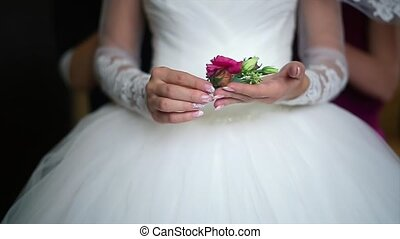 Bride is Holding a Red Boutonniere Flowers.