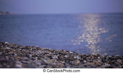 Moon Path on beach - On pebble beach in water reflects moon...