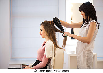 Professional hairdresser drying hair of her client - Best...
