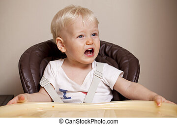 Two year baby boy sitting at the dinner table - Portrait of...