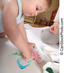 Fingerpainting - Little boy is painting using his fingers