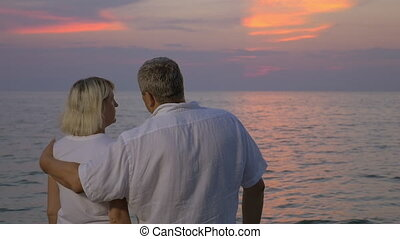 Hugs of love during sunset over sea - Slow motion of senior...