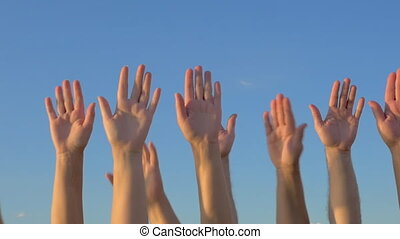 Hands up on blue sky background - Slow motion of many hands...