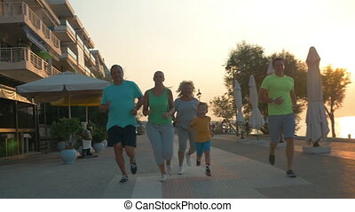 Happy family finishing evening run on resort - Slow motion...
