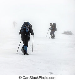 Mountain hiking group in snow storm - Mountain hiking group...