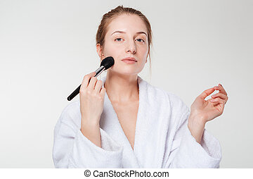 Cute woman with cosmetic brush isolated on a white...