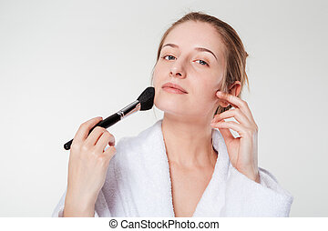 Woman applying blusher isolated on a white background