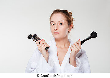 Young woman holding makeup brushes isolated on a white...