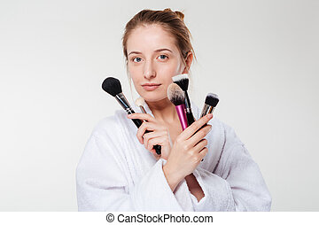 Beautiful woman holding makeup brushes isolated on a white...