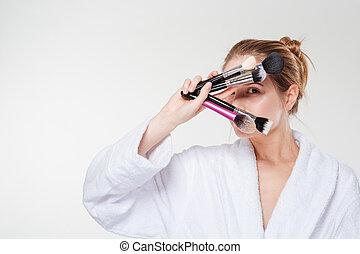 Woman in bathrobe holding makeup brushes isolated on a white...