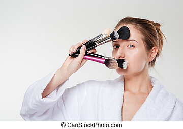 Woman in bathrobe holding makeup brushes - Young woman in...