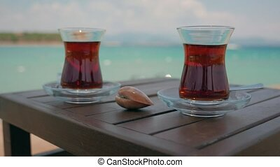 Two glasses of turkish tea on the table with Mediterranean Sea on the background in Turkey. 4k