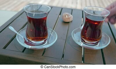 Two glasses of turkish tea on the table with wooden table on the background in Turkey. 4k
