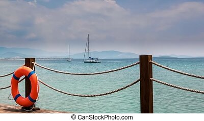 Wooden pier and orange life ring with anchored sailing yacht...